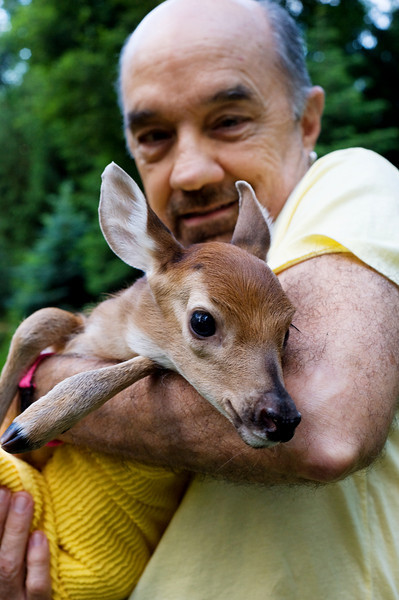 man with baby deer