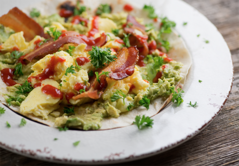 Crispy bacon, soft scrambled egg, velvety avocado and Sriracha nestle on a warmed tortilla in this breakfast tacos recipe that is perfect any time of day!
