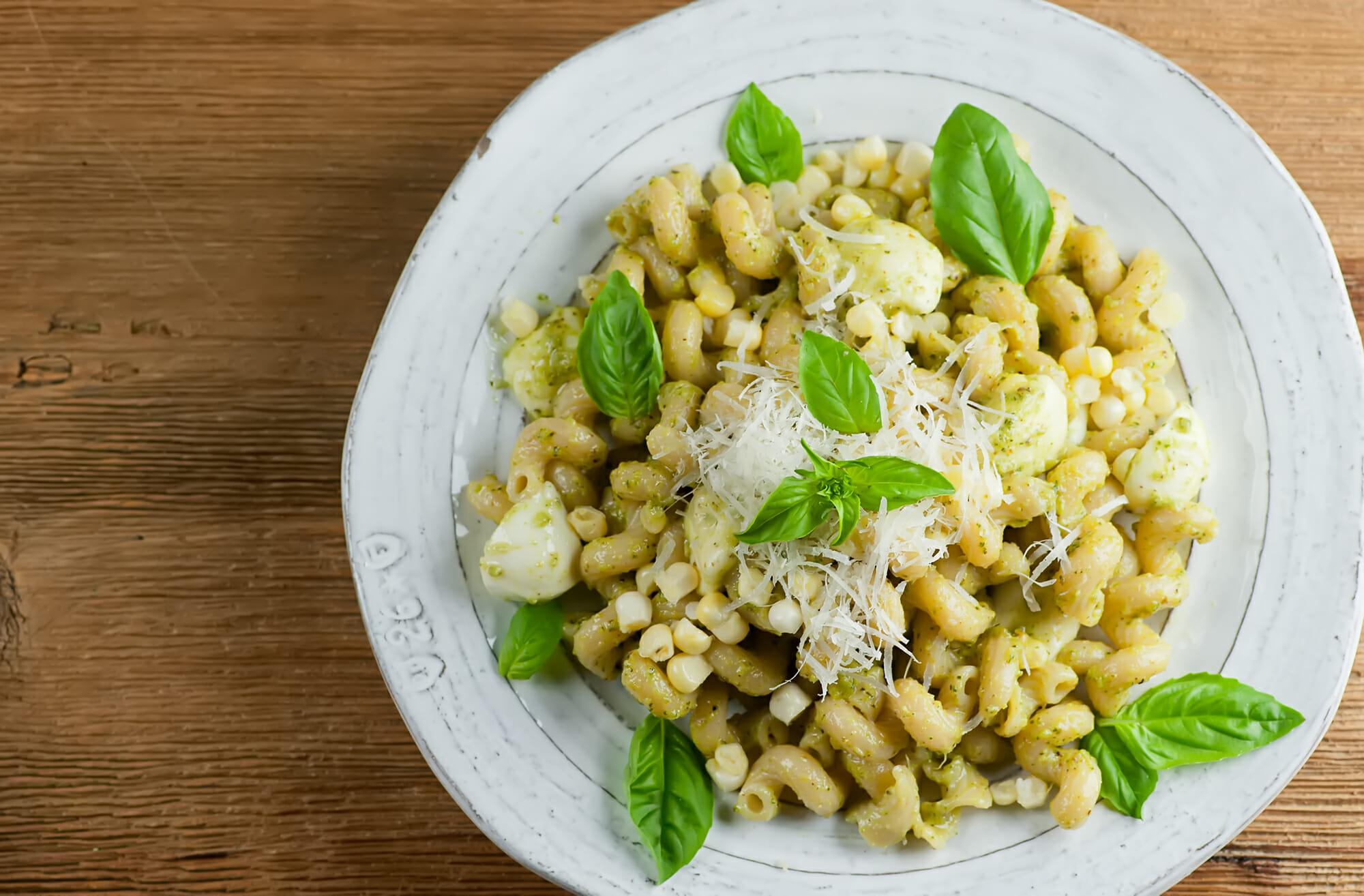 plate of pesto pasta with fresh corn and mozzarella